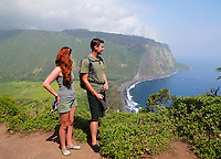 Two hikers look out at Waipi'o Bay, with Waipi'o Valley to the left, Hamakua, Big Island.