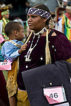 Native African American mother holding son in Inter tribal Dancing a celebration of ethnic Native American pride and heritage at Thunderbird Pow Wow
