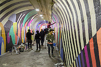 A  portion of  the 900-foot long 191st Subway station connecting tunnel, is painted by artists Jessie Unterhalter and Katey Truhn, and newly decorated by artists hired by the New York City Dept. of Transportation on Thursday, May 21, 2015. The artists, COPE2, Queen Andrea, Nick Kuszyk, Cekis and Jessie Unterhalter and Katey Truhn were chosen in a competitive process by the DOT. The tunnel has recently received upgraded LED lighting and with the addition of the murals has been turned into an art gallery. (© Richard B. Levine)