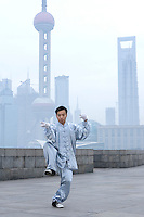 A man practices the Chinese martial art tai-chi at dawn on the Bund, in front of the Oriental Pearl tower (left) and the World Financial Center (right), in Shanghai, China, on February 1, 2009. Photo by Lucas Schifres/Pictobank