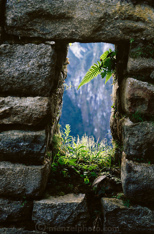 Detail of a stone window frame and the view through it at the Inca ruins at Machu Picchu, Peru.