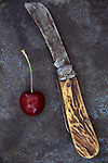 Single dark red cherry with stalk lying next to old pocket knife with ivory handle on tarnished metal