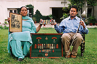 Mrs Paramjit Kaur and her son Sandeep Kang outside their home, the former British Officers' Mess in the Jalandhar cantonement on the Grand Trunk Road. Their family have a long tradition of service with the British and Indian armies, they sit with their family's medals. The photograph she holds shows her grandfather with King Edward VIII when he served the Royal Family.