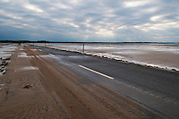 looking towards mainland from sand covered road from Lindisfarne - Holy island, at low tide, Lindisfarne, England.  The road is only passable for a few hours around low tide, tidal charts are posted listing opening times