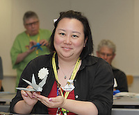 New York, NY, USA - June 24, 2012: Deb Pun, from California, holds a complex Origami model of a swallow, designed by Sipho Mabona, which she has folded at a class he is teaching during the OrigamiUSA 2012 convention held at Fashion Institute of Technology in New York City. This model is folded from one square sheet of paper.