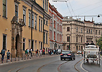 A horse carriage goes down a busy street in Krakow, Poland