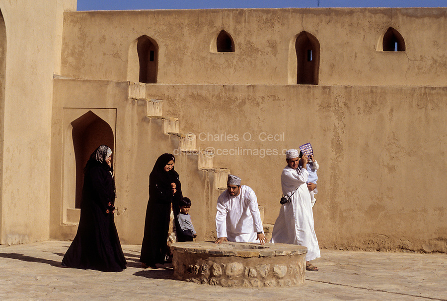 Jabrin, Oman.  Omani Tourists Looking at the Well in the Courtyard of Jabrin Fort.