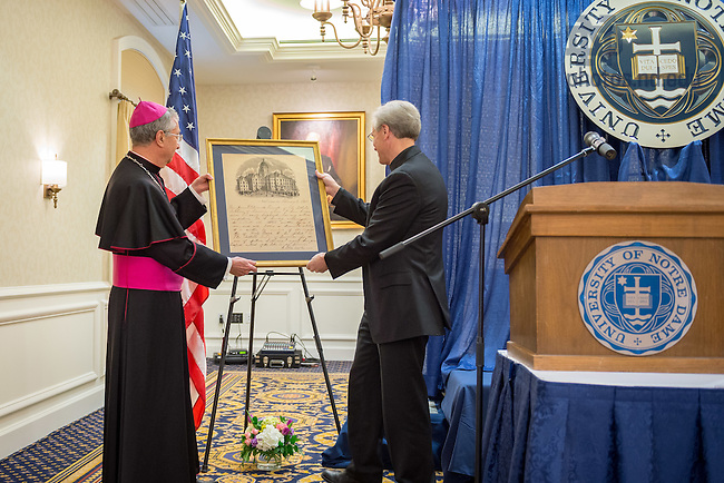 "May 9, 2016; University of Notre Dame President Rev. John I. Jenkins, C.S.C. presents Archbishop Jean-Louis Brugues, Archivist and Librarian of the Holy Roman Church, with a gift at a ceremony where Archbishop Brugues and Fr. Jenkins signed a memorandum of understanding for collaboration and exchanges between the Vatican Library and Notre Dame.  The signing ceremony was in conjunction with the conference ""The Promise of the Vatican Library,"" an international academic conference highlighting the holdings of the Vatican Library and opportunities for future research.(Photo by Matt Cashore/University of Notre Dame)"