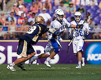Sam Solie (23) of Duke is checked by Sean Rogers (18) of Notre Dame during the NCAA Men's Lacrosse Championship held at M&T Stadium in Baltimore, MD.  Duke defeated Notre Dame, 6-5, to win the title in overtime.