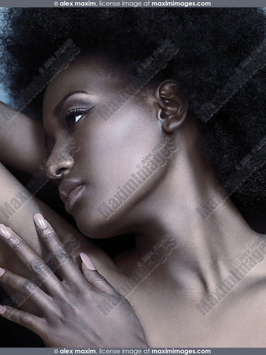 Artistic beauty portrait of a young black woman face with shiny silver metallic skin