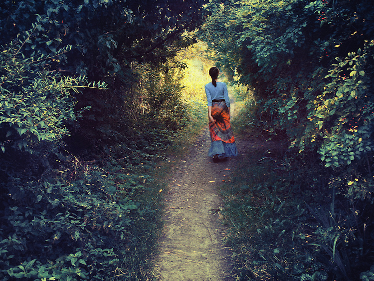 A woman in a blue & red outfit, walking down a path among trees, towards  golden light at the end of the path.