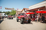 Red Jeeps of the Motherlode Rock Crawlers 4wd group with jazzed-up jeeps. Downtown main street during the Independence Day celebration Main Street, Mokelumne Hill, California