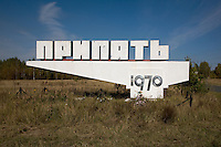 Concrete entrance sign to Pripyat. Now a memorial, it is surrounded by a steel chain  and plastic flowers. <br />