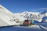 Truck crosses Atigun pass on the snow covered Dalton Highway, Brooks range, Arctic, Alaska