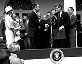 United States President John F. Kennedy congratulates astronaut Alan B. Shepard, Jr., the first American in space, on his historic May 5th, 1961 ride in the Freedom 7 spacecraft and presents him with the National Aeronautics and Space Administration (NASA) Distinguished Service Award, in Washington, D.C. on May 6, 1961.  Shepard's wife, Louise (left in white dress and hat), and his mother were in attendance as well as the other six Mercury astronauts, including Colonel John H. Glenn, Jr. and other NASA officals, some visible in the background..Credit: NASA via CNP
