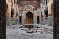 Low angle view of main courtyard with pool, Sahrij Medersa, (Medersa des Andalous), 1321, Fez, Morocco, pictured on February 23, 2009 in the morning. The Sahrij Medersa takes its name from the pool in its courtyard, (sahrij means basin). Green and white minarets crown the theological school founded by Merinid sultan Abou al-Hassan and attached to the Al-Andalous mosque.  It is decorated with ornate  dark cedar panels (mashrabiya), decorated tiles (zellij), marble pavings and intricate plasterwork. Fez, Morocco's second largest city, and one of the four imperial cities, was founded in 789 by Idris I on the banks of the River Fez. The oldest university in the world is here and the city is still the Moroccan cultural and spiritual centre. Fez has three sectors: the oldest part, the walled city of Fes-el-Bali, houses Morocco's largest medina and is a UNESCO World Heritage Site;  Fes-el-Jedid was founded in 1244 as a new capital by the Merenid dynasty, and contains the Mellah, or Jewish quarter; Ville Nouvelle was built by the French who took over most of Morocco in 1912 and transferred the capital to Rabat. Picture by Manuel Cohen.