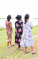 Three young women on Jaluit Atoll, looking towards the lagoon.