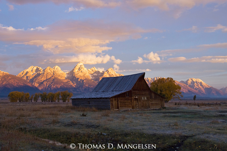 The early morning rays of the sunrise illuminate the Tetons behind the Moulton barn in Grand Teton National Park, Wyoming.