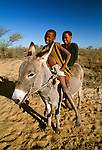 San youths on a donkey, Kalahari Desert, Botswana