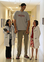 UVa endocrinologists Dr. Cristina Gherghe, left, and Dr. Mary Lee Vance, right, stand with the world's tallest man Sultan Kosen Friday at the UVa Medical Center. Kosen, who stands 8ft. 2inches tall from Turkey, was at the medical center for radiation treatment. Photo/The Daily Progress/Andrew Shurtleff