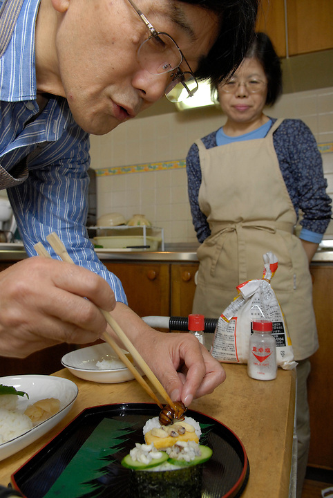 "Shoichi and Chisato Uchiyama preparing insect sushi in their kitchen at home in Tokyo. Tokyo resident Shoichi Uchiyama is the author of ""Fun Insect Cooking"". His blog on the topic gets 400 hits a day. He believes insects could one day be the solution to food shortages, and that rearing bugs at home could dispel food safety worries."