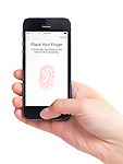 Close up of a hand holding iPhone 5 with a thumb being scanned by a fingerprint sensor. Touch ID security concept. isolated on white background