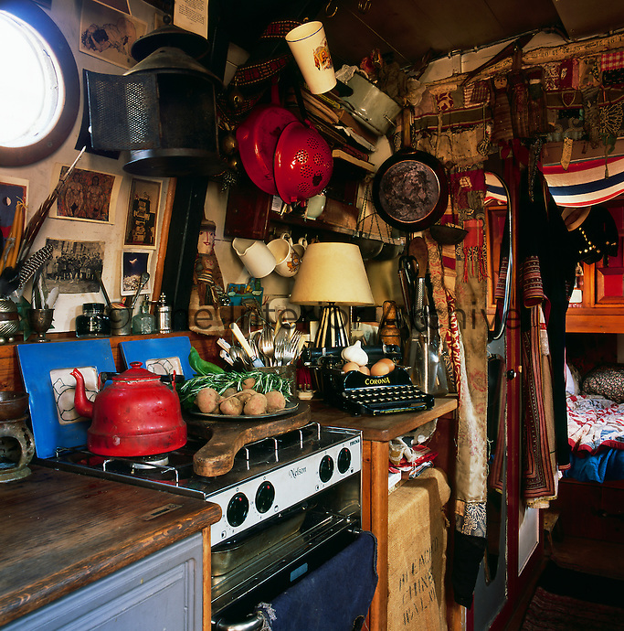 The cosy interior of a canal boat decorated in a bohemian style. The kitchen area with a view through to the sleeping cabin