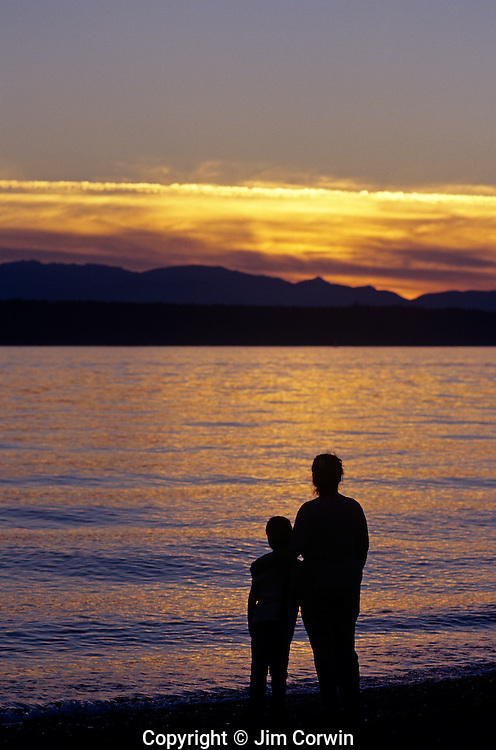 Mother and daughter holding each other along Edmonds Beach at sunset Washington State USA