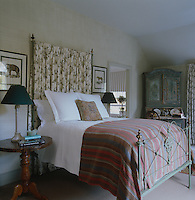 A delicate floral-patterned fabric hangs behind this antique iron wrought bed