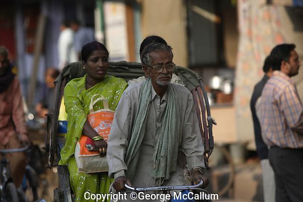 Rickshaw wallah or puller with Customers in back. Varanasi, Uttar Pradesh, India