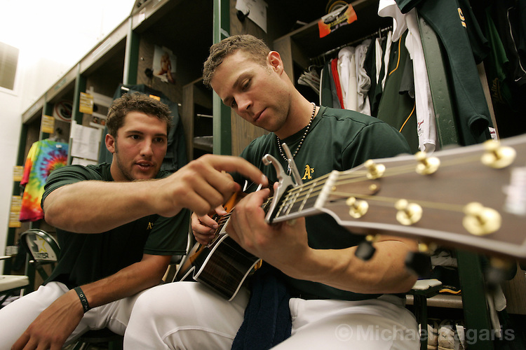 OAKLAND, CA - JULY 16:  Huston Street and Rich Harden of the Oakland Athletics practice the guitar in the clubhouse before the game against the Texas Rangers at McAfee Coliseum on July 16, 2005 in Oakland, California. The Rangers defeated the A's 10-8. (Photo by Michael Zagaris /MLB Photos via Getty Images)