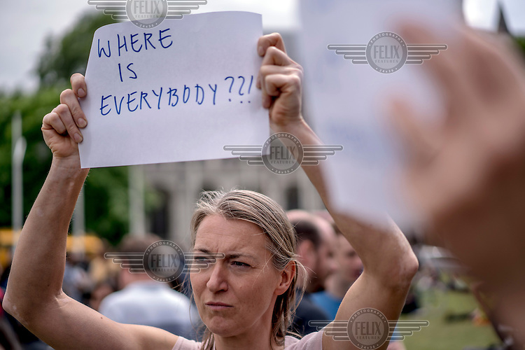 A woman holds a placard that reads: 'where is everybody' at a demonstration in Parliament Square protesting the victory of the 'leave' (the EU) side in the EU reeferendum.