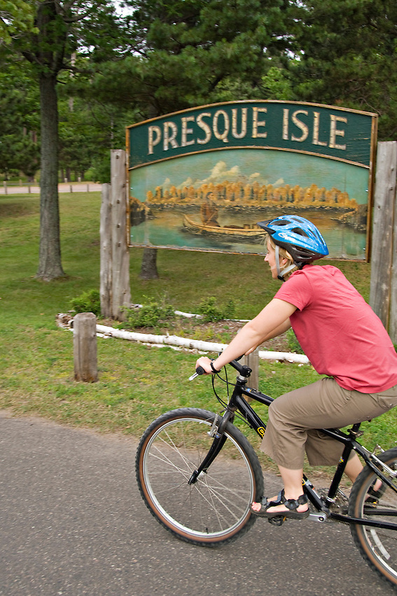 A bicyclist at the entrance to Presque Isle Park in Marquette Michigan.