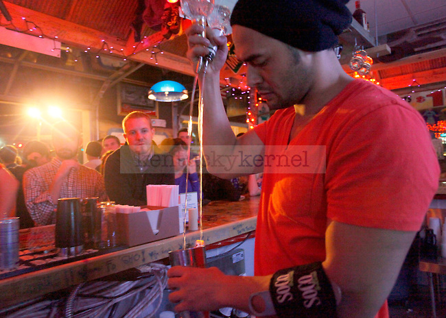 UK alum and former political cartoonist for the Kentucky Kernel Brennan Bandy watches UK alum and Tin Roof bartender Topher Aldridge make a drink Friday night during the South Limestone Block Party to benefit the Huntsman Cancer Foundation..Photo by Zach Brake | Staff