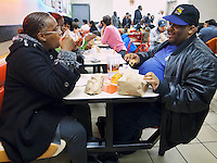 USA. New York City. An afro-american couple eats at Burger King. Hamburgers, french fries, ketchup and sodas. Fast food. Junk food and soft drinks. Baseball cap. 22.10.2011 © 2011 Didier Ruef