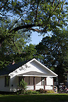 Small white house on shady street, in summertime in Midland, Michigan, USA