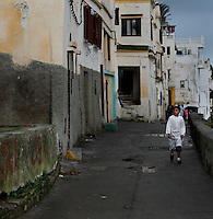Medina, Tangier, Morocco pictured on December 18, 2009. A boy walks confidently along a street, past the old houses with crumbling white washed walls, balconies and roof terraces. Tangier, the 'White City', gateway to North Africa, a port on the Straits of Gibraltar where the Meditaerranean meets the Atlantic is an ancient city where many cultures, Phoenicians, Berbers, Portuguese and Spaniards have all left their mark. With its medina, palace and position overlooking two seas the city is now being developed as a tourist attraction and modern port. Picture by Manuel Cohen