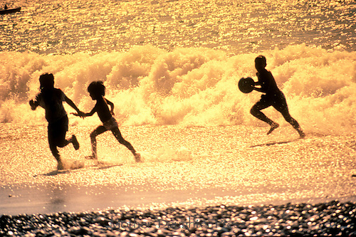 Kids playing on beach in silhouette