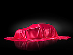 New car model on a stand under red fabric presentation concept isolated on black background