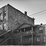 Old 2 story house and porch with child next to abandoned hotel. Somewhere in Pennsylvania. 1977