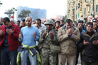 An Egytpian army soldier prays alongside protesters at Cairo's main Tahrir (Liberation) Square.