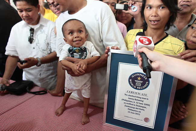 Concepcion Balawing, speaks to reporters after her son Junrey (center) was recognized by Guinness World Records as the world's shortest living man. The 18-year-old resident of the town of Sindangan, Philippines stands only 23.5 inches tall. June 12, 2011. DREW BROWN/MCT
