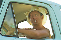 Man wearing a cowboy hat smoking with his arm resting on the door of his pickup truck