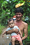 A proud father poses with his son for a portrait in Mekong Delta, south of Can Tho, Vietnam. Sept. 30, 2011.