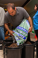 "A student pours mulch into pots at Orange Coast College's Ornamental Horticulture Club's in-progress installation at the 2012 South Coast Plaza Spring Garden Show in Costa Mesa, CA.  The theme for this year's show is ""healing gardens"", and the OCC team is installing a ""garden for the blind,"" which will be complete with a braille world globe and braille labels.  This picture was taken Tuesday April 25, 2012 at ~11pm, as the team was working frantically to meet their Thursday-morning deadline."