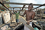A man in the Haitian village of Dabonne builds a new temporary shelter to house his family, following the destruction of their home in a January 12 earthquake. He uses old lumber salvaged from the ruins of his old house.