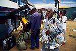 SOWETO, SOUTH AFRICA MARCH 14: A man sells goods as passengers board to long-distance bus at Baragwanath taxi station on March 14, 2005 in Soweto, Johannesburg, South Africa. The station is the largest in the township and tens of thousands of people use it every day for travel around Johannesburg and around the country. Soweto is South Africa?s largest township and it was founded about one hundred years to make housing available for black people south west of downtown Johannesburg. The estimated population is between 2-3 million. Many key events during the Apartheid struggle unfolded here, and the most known is the student uprisings in June 1976, where thousands of students took to the streets to protest after being forced to study the Afrikaans language at school. Soweto today is a mix of old housing and newly constructed townhouses. A new hungry black middle-class is growing steadily. Many residents work in Johannesburg, but the last years many shopping malls have been built, and people are starting to spend their money in Soweto.  .(Photo by Per-Anders Pettersson/Getty Images).