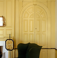 A built-in cupboard with arched doors on one side of the fireplace conceals a collection of antique glass and porcelain