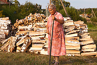 Visokoye, Ivanova Region, Russia, 04/08/2012..An old woman walks past piles of firewood and the village well in Visokoye, some 200 miles east of Moscow.