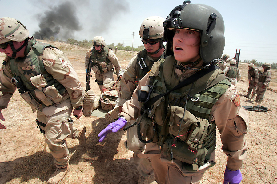 Spc. April Krueger (foreground) - a flight medic with the 50th Medical Company (Air Ambulance), 101st Airborne Division - guides fellow soldiers as they carry an Iraqi soldier wounded by a car bomb toward her crew's UH-60 Blackhawk medevac helicopter for a flight to the 86th Combat Support Hospital in Baghdad's Green Zone on June 14, 2005.